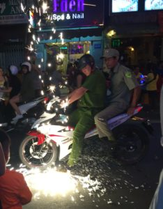 An unimpressed policeman stamps on live firework to end festivities. New Year in Ho Chi Minh City is crazy!