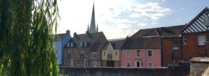 One of Norwich's cathedrals overlooking riverside houses in Norfolk