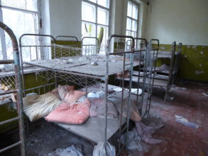The beds inside this kindergarten remain intact and largely undisturbed, except for the sheets which drape along the floors.