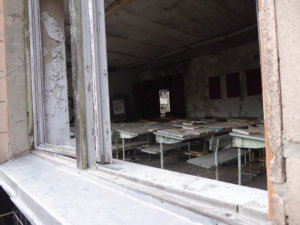 An old classroom appears untouched after the accident, with workbooks still laying on the desks.