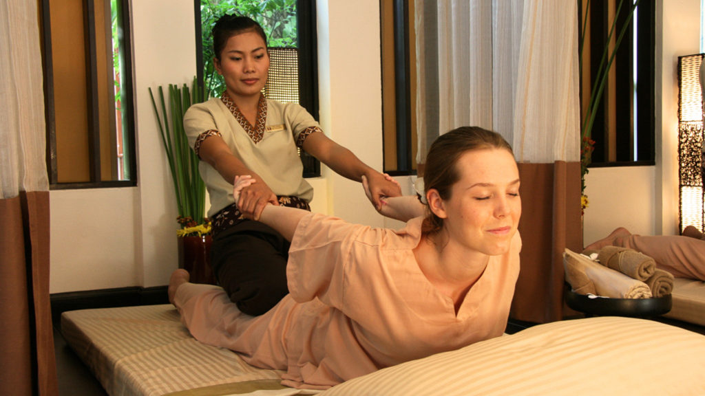 Woman pulls woman's arms during Thai Massage