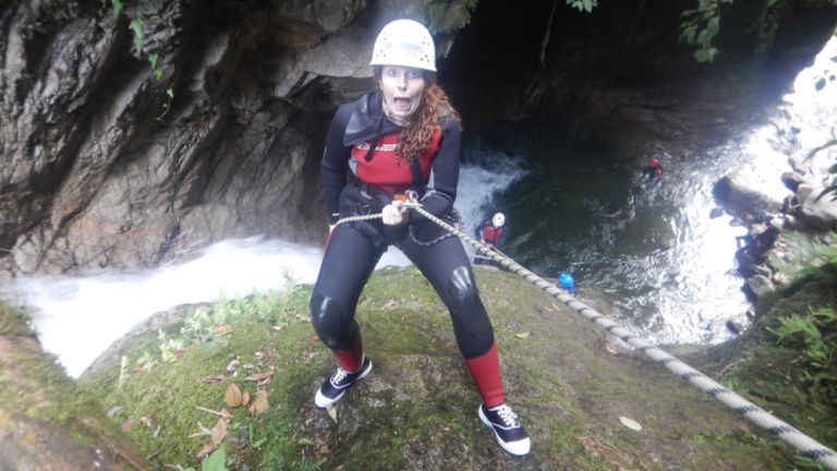 Nervous girl abseiling next to waterfall