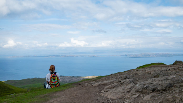 Girl overlooks sea and islands in Scottish highlands