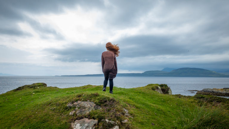 Girl stands on cliff edge, looking at islands.
