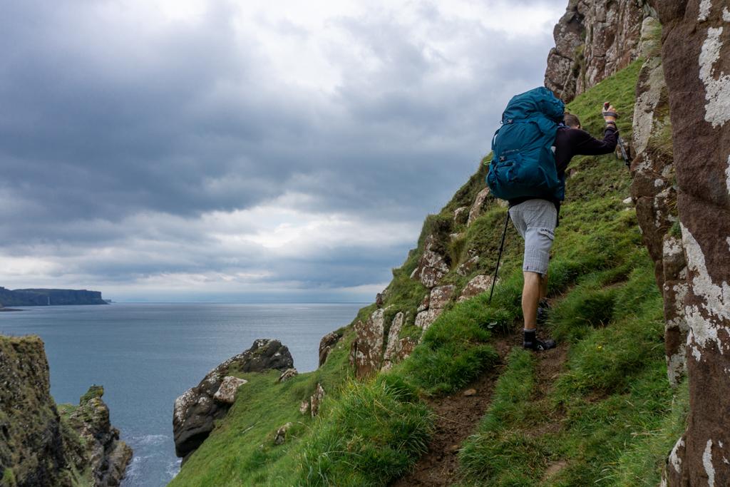 Man hikes up steep cliff, Isle of Skye