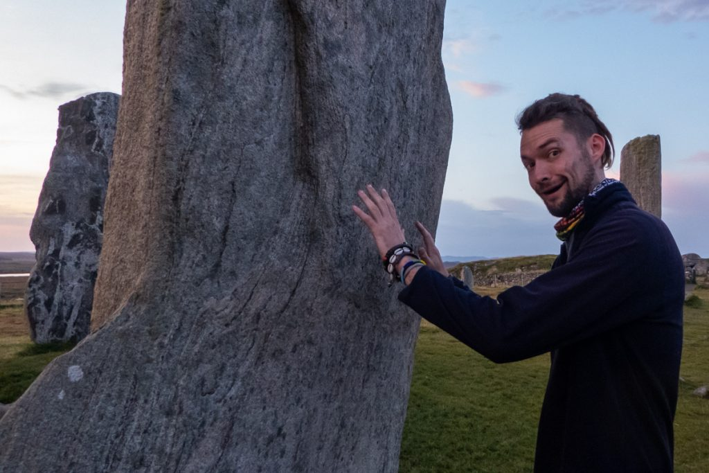 Man pretends to touch standing stones
